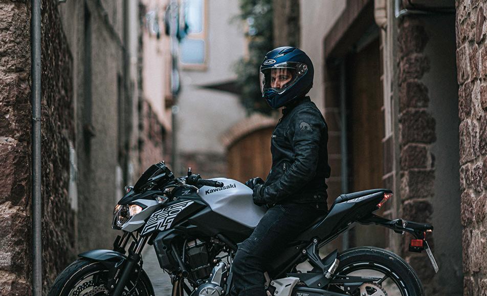 Motorradfahrer auf Motorrad zwischen Häusern